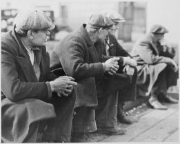 Row_of_men_at_the_New_York_City_docks_out_of_work_during_the_depression,_1934_-_NARA_-_518288
